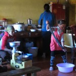 Everyone going about their morning chores (from right to left): washing, preparing food, making cheese!